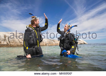 Happy scuba diver couple in ocean celebrating dive with a high five - Stock Image