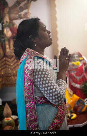 Profile of a devout Hindu woman and priest praying with her hands clasped in a temple in Queens, New York City. - Stock Image