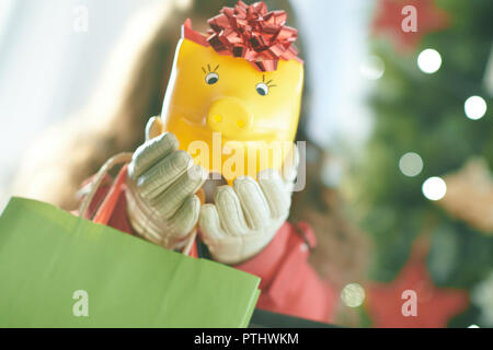 Closeup on yellow piggy bank in a hand of woman with shopping bags near Christmas tree - Stock Image