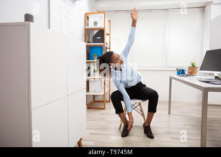 Young Businesswoman Doing Yoga Standing In Front Of Office Desk - Stock Image