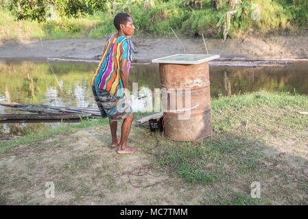 A Papuan woman checking a solar panel on a can, Swagup Village, Upper Sepik, Papua New Guinea - Stock Image