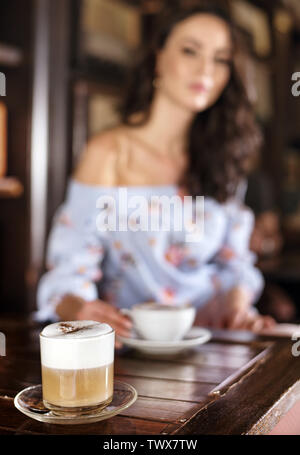 Blurred portrait of a brunette woman in a coffee shop - Stock Image