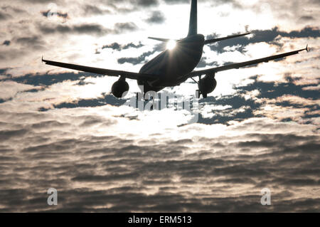 Commercial jet on final approach, in silhouette with backdrop of scatter cloud and sun behind aircraft tail - Stock Image