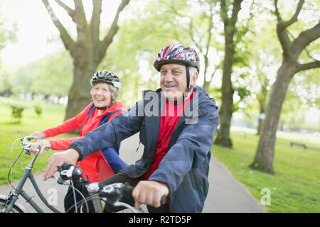 Active senior couple riding bikes in park - Stock Image