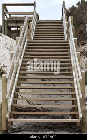 Wooden staircase leading up away from the beach. - Stock Image
