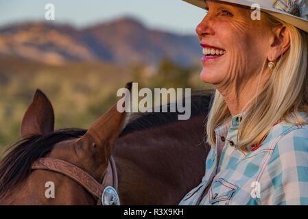 USA, California, Parkfield, V6 Ranch close-up detail portrait of blond cowgirl with her horse (MR) - Stock Image