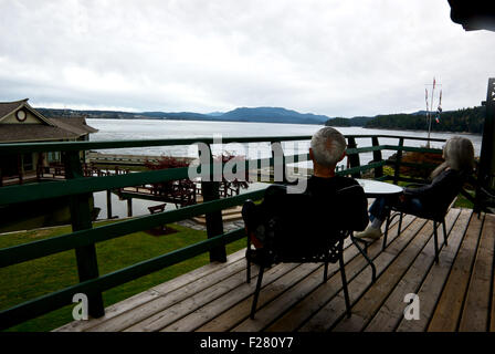 Couple sitting on sundeck looking over Discovery Passage April Point Resort Quadra Island BC Canada - Stock Image