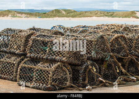 Lobster pots stacked in pile on a harbour with a sandy bay in the background - Stock Image