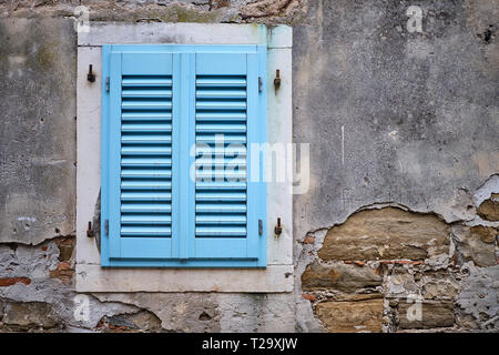 window with closed blue shutters.  Texture concrete walls, crumbling and falling of revealing bricks - Stock Image