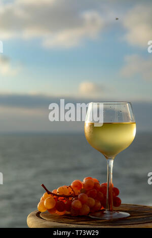 Aperitif cold white wine served in glasses with pink grapes on outdoor tessace witn sea view close up - Stock Image