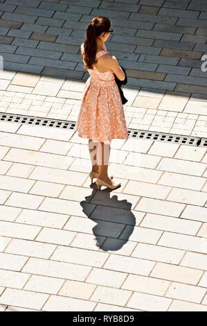 brunette woman with pink salmon dress standing on the street in summer day - Stock Image