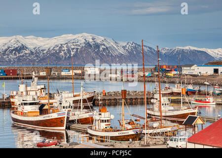 13 April 2018: Husavik, North Iceland - Whale watching boats in the harbour on a bright spring day. - Stock Image