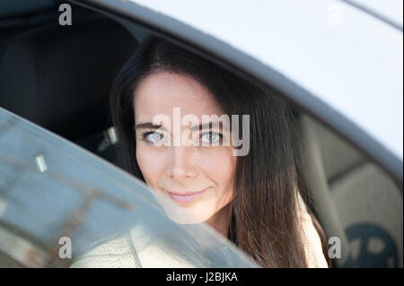 Middle aged hispanic woman in car looking out thru open car window, strong eyes - Stock Image
