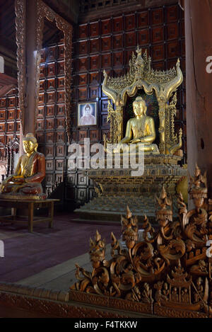 Interior with  central   golden buddha in  the historic teak wood temple of  Shwe in bin Kyaung in Mandalay, Burma - Stock Image