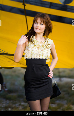 Fanciful young woman is waiting besides Yellow biplane airplane - Stock Image