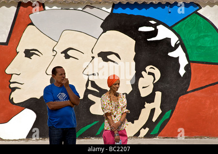 Cuban man and woman standing in front of a typical Cuban socialist wall painting. Havana, Cuba - Stock Image