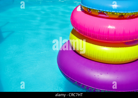Inflateable colorfull tubes in swimming pool - Stock Image