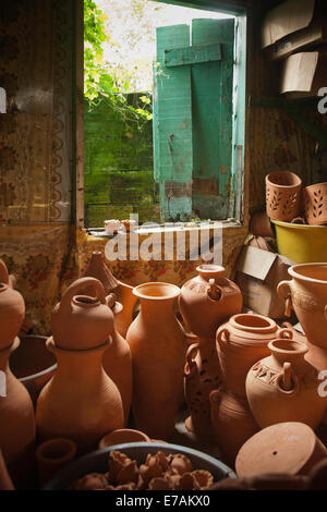 Clay pots and deyas and a blue shuttered window at Radika pottery in Chaguanas, Trinidad - Stock Image