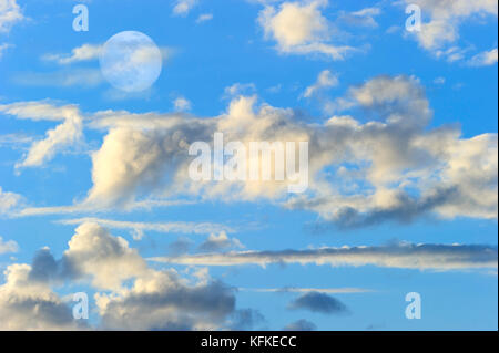 Moon clouds is a colorful surreal fantasy like pink and blue cloudscape with a magical surreal full moon rising - Stock Image