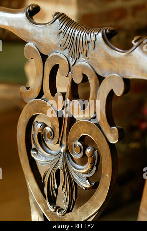 Ornately carved wooden chair back in oak colour - Stock Image
