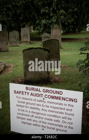 Kelso chruch graveyard in Scotland. Notice of a safety audit (many of the gravestones were laid flat after this for safety). - Stock Image