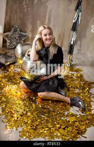 Amazing cute lady celebrating new year birthday party, posing in gold shine background and throwing colorful confetti with silver baloons - Stock Image