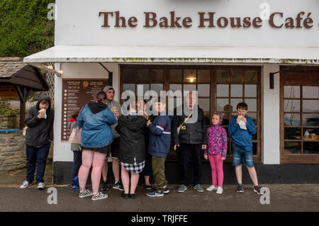 Lynmouth Devon England UK. Family sheltering from the roain eating their lunch. May 2019 Lynmouth is a village in Devon, England, on the northern edge - Stock Image