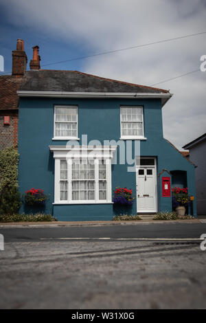 A blue old english cottage with a red post box in the wall - Stock Image