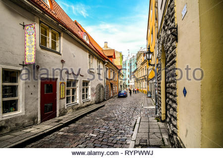 Tourists walk down a picturesque cobblestone street in a residential and business area of the medieval old town in Tallinn, Estonia - Stock Image
