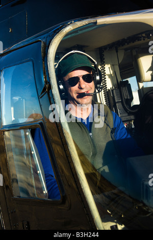 Portrait of helicopter pilot sitting in cockpit looking at viewer - Stock Image