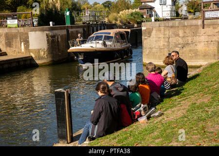England, Berkshire, Goring on Thames, visitors sat on riverbank in sunshine watching boat leave River Thames locks - Stock Image