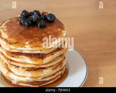 A large stack of pancakes covered with maple syrup and blue berries - Stock Image