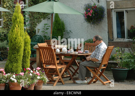 middle aged man sitting at tea table outside cafe in Eyam, Derbyshire - Stock Image