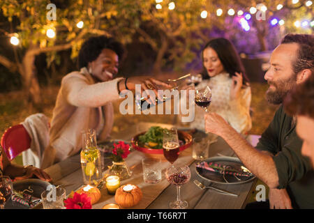 Friends pouring and drinking wine, enjoying dinner garden party - Stock Image