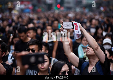 Protester take photos during the mass rally. Nearly two million people joined the demonstration in another round of protest demanding the Hong Kong government to withdraw the extradition bill.Despite the Chief Executive Carrie Lam's attempt to ease the heightened tension by agreeing to suspend the controversial bill, close to 2 million people participated in Sunday's rally, according to the organizers. The protesters called for the withdrawal of the controversial extradition bill, the release and non-prosecution of the people arrested due to the cause, investigation of whether excessive force - Stock Image