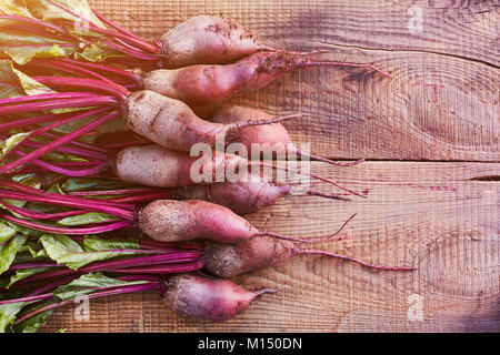Bunch of fresh organic beetroots on wooden rustic table. A half of a wooden table is free for the paste text on - Stock Image