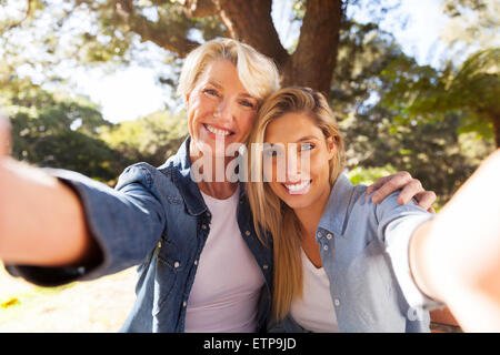 happy senior woman and daughter taking selfie together - Stock Image