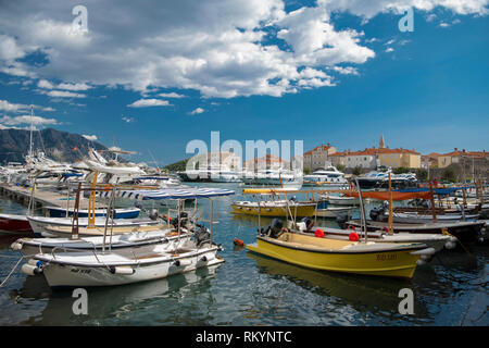 Colourful boats in Budva's historic marina in Montenegro tourist town. - Stock Image