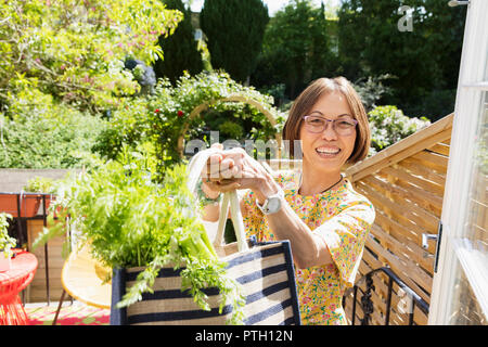 Portrait enthusiastic senior woman holding bag of fresh vegetables on balcony - Stock Image