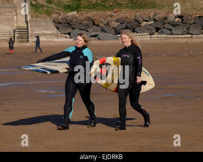 Two middle aged female surfers heading down the beach carrying surfboards, Bude, Cornwall, UK - Stock Image