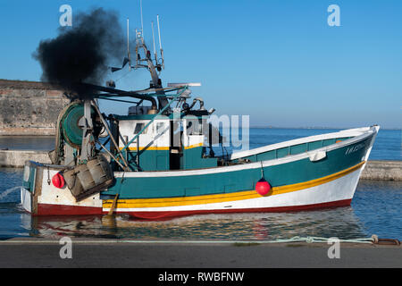 France, Oléron, 2018.  Black diesel fumes exhaust, generated by a small fishing boat as the Captain prepaires the trawler to leave the port of  Châtea - Stock Image
