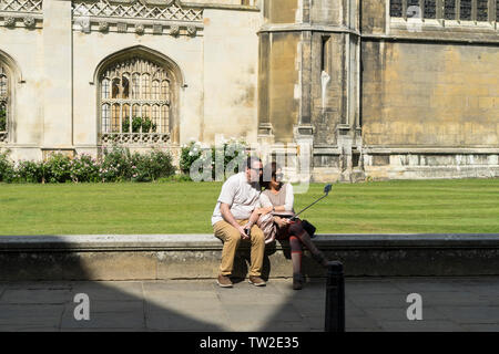 Couple sat on wall taking selfie in front of Kings college Cambridge 2019 - Stock Image