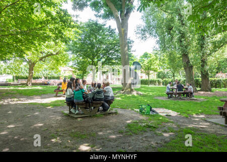 Friends sit together at picnic tables in Holland Park, London. - Stock Image