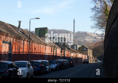 Industrial buildings on Holmes Road with Wainhouse Tower in the background, Sowerby Bridge, West Yorkshire - Stock Image