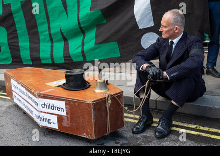 London, UK. May 11th 2019. National Demonstration for Palestine. Thousands of activists marched from Portland Place to Whitehall. Organised by the Palestine Solidarity Campaign, Stop the War Coalition, Palestinian Forum in Britain, Friends of Al- Aqsa & Muslim Association of Britain. Pictured, Palestine activist sitting in Whitehall with coffin, with Israelis execute Palestinian children and Jeremy Hunt does nothing written on coffin side. Credit: Stephen Bell/Alamy Stock Photo - Stock Image