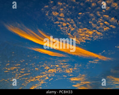 A spectacular brightly coloured atmospheric Orange and Blue cloudy sky cloudscape featuring an Altocumulus and Cirrus cloud formation in a mid blue sky - Stock Image