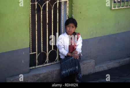 A young, indigenous Tzutujil Maya girl sitting outside her house. San Lucas Tolimán, Lake Atitlan, Guatemala. - Stock Image