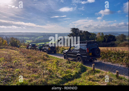 Land Rovers passing cyclists on a 'Byway Open To All Traffic' at Newlands Corner on the North Downs. Guildford, Surrey, England. - Stock Image