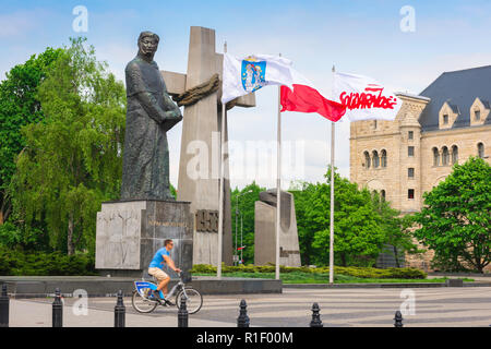 Poznan monument, a cyclist rides his bike past the Monument to the Victims of June 1956 in Adam Mickiewicz Square (Plac Mickiewicza), Poznan, Poland. - Stock Image