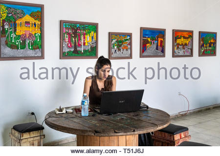'El Mejunje de Silverio' indoors details of the famous place and tourist attraction. Young woman studying or working in the Galleria. The local landma - Stock Image